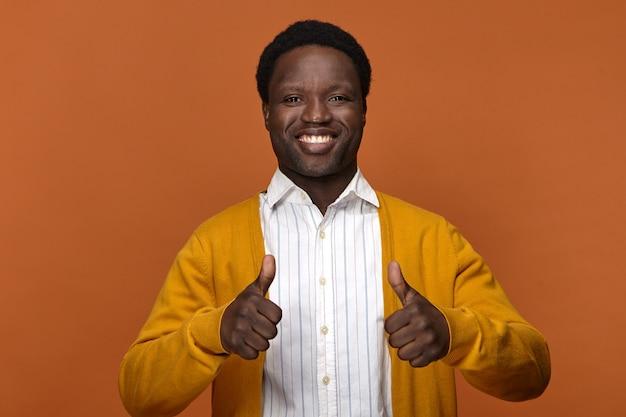 Glücklicher aufgeregter junger dunkelhäutiger kerl, der breit lächelt und seine weißen perfekten zähne zeigt, die schläge als zeichen des positiven denkens oder der zustimmung aufgeben. erfolg, wie gute laune und positivität konzept