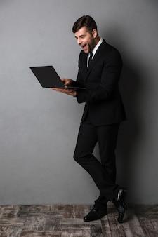 Glücklicher aufgeregter junger geschäftsmann, der laptop-computer verwendet