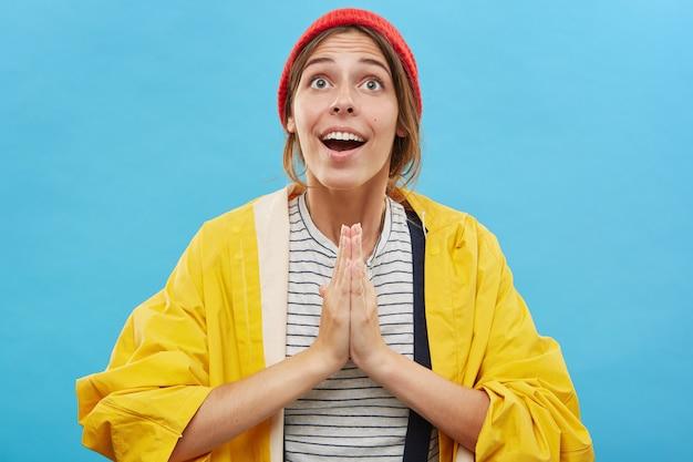 Glücklicher aufgeregter schöner weiblicher starker gläubiger, der hut und regenmantel trägt, fröhlichen blick hat, breit lächelt, hände im gebet hält, gott für liebe, glück und wohlbefinden dankbar fühlt