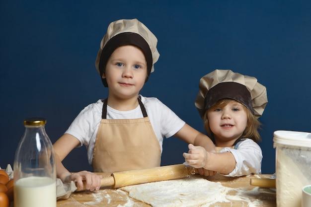Glücklicher aufgeregter schuljunge, der teig mit nudelholz flach drückt, während seine kleine schwester ihm hilft. zwei süße kindergeschwister, die zusammen pizza machen