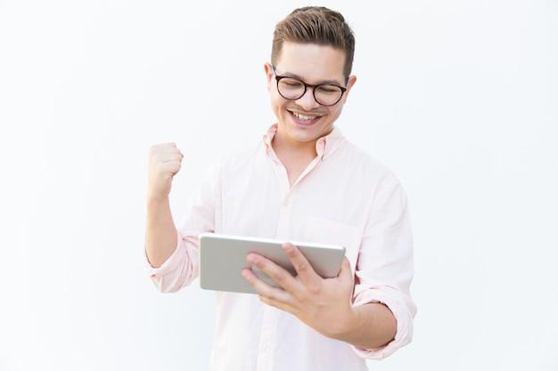 Glücklicher aufgeregter tablettenbenutzer, der erfolg feiert