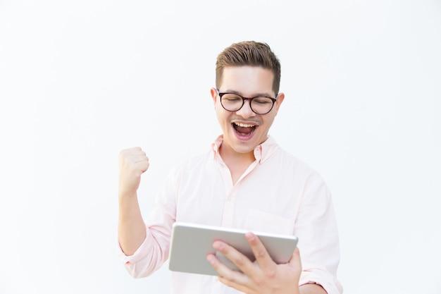 Glücklicher aufgeregter tablettenbenutzer, der nach freude schreit