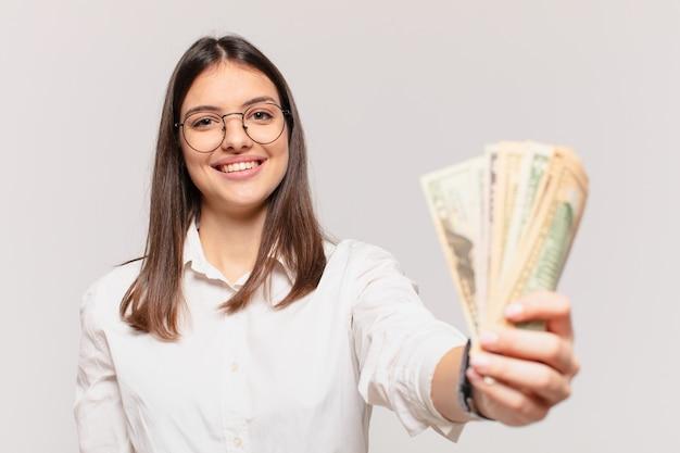 Glücklicher ausdruck der jungen hübschen frau und halten von dollarbanknoten