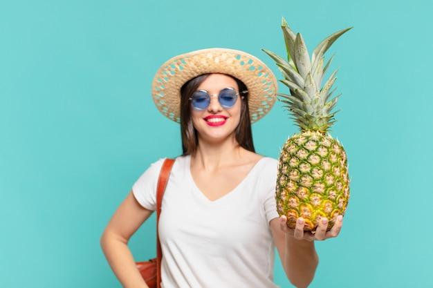 Glücklicher ausdruck der jungen reisendenfrau, die eine ananas hält