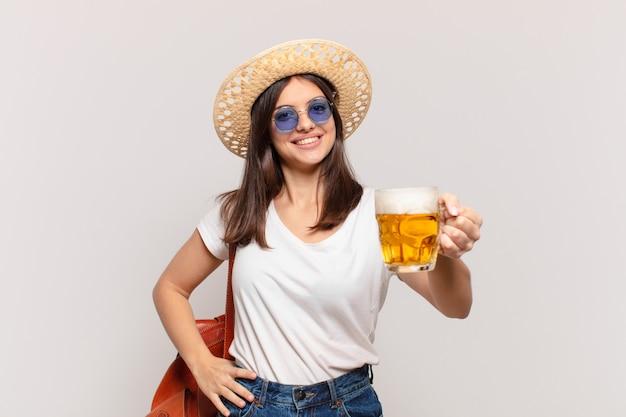 Glücklicher ausdruck der jungen reisendenfrau und halten eines bieres