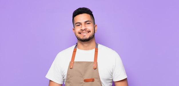 Glücklicher ausdruck des jungen hispanischen mannes. kochkonzept