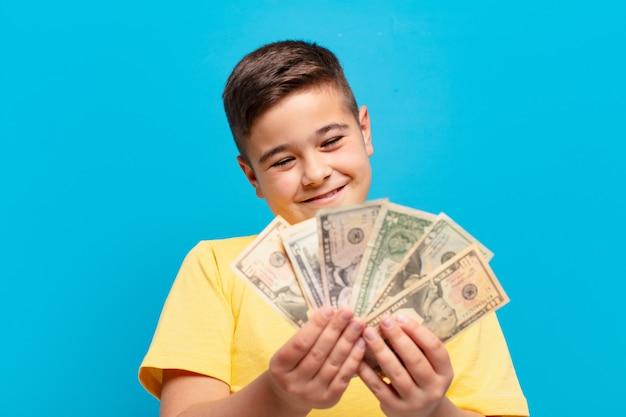 Glücklicher ausdruck des kleinen jungen mit dollarbanknoten
