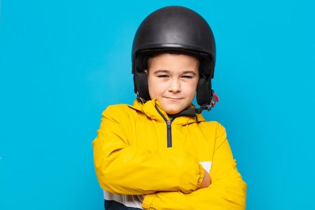 Glücklicher ausdruck des kleinen jungen. motorradhelmkonzept