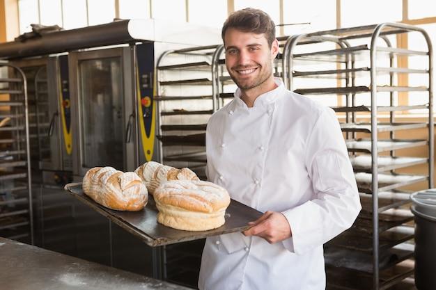 Glücklicher bäcker, der behälter mit brot zeigt