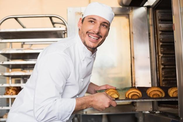 Glücklicher bäcker, der frische hörnchen herausnimmt