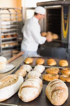 Glücklicher bäcker, der frische laibe herausnimmt