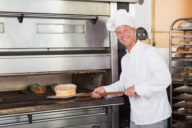 Glücklicher bäcker, der frisches laib herausnimmt