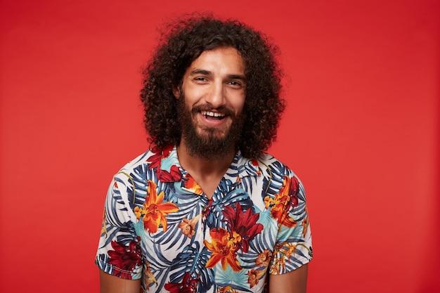 Glücklicher bärtiger brünetter mann mit langen lockigen haaren, die freudig lachen, während sie schauen, im hemd mit blumendruck stehend