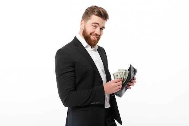Glücklicher bärtiger geschäftsmann, der geldbeutel mit geld hält