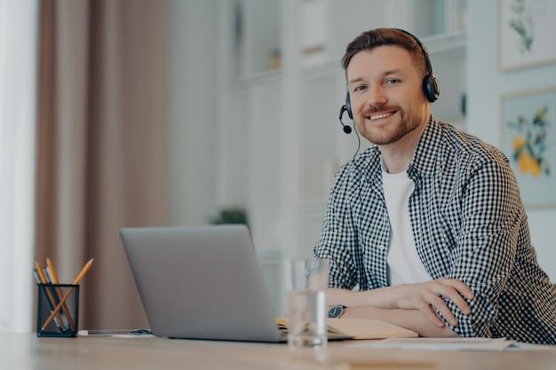 Glücklicher bärtiger gutaussehender mann in freizeitkleidung und kopfhörern, der im home office sitzt und in die kamera lächelt, fröhlicher männlicher freiberufler mit online-chat auf dem laptop. remote-arbeit zu hause