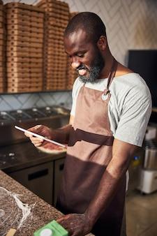 Glücklicher bärtiger gutaussehender mann in schürze steht in der restaurantküche und hat spaß mit tablet
