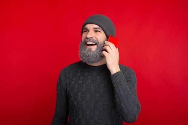 Glücklicher bärtiger hipster-mann, der über rotem raum steht und auf smartphone spricht