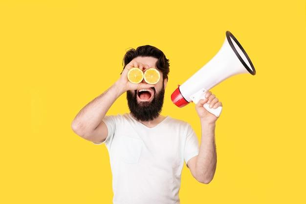 Glücklicher bärtiger hipster-mann mit geschnittener zitrone auf den augen, die durch ein megaphon schreien