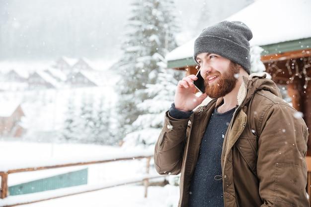 Glücklicher bärtiger junger mann, der im winter draußen am handy telefoniert
