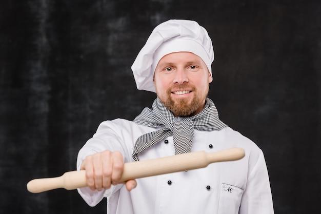 Glücklicher bärtiger koch in der uniform, die hölzernen nudelholz vor der kamera hält, während er sie ansieht