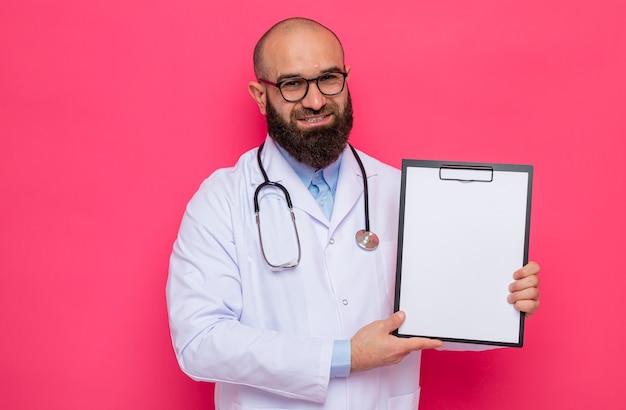 Glücklicher bärtiger mann arzt im weißen kittel mit stethoskop um den hals mit brille, die eine zwischenablage mit leeren seiten hält und in die kamera blickt, die zuversichtlich auf rosa hintergrund lächelt