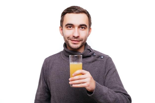Glücklicher bärtiger mann, der ein glas orangensaft hält und die geste mit dem daumen nach oben isoliert auf weißer wand zeigt