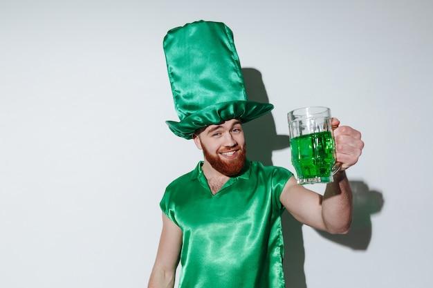 Glücklicher bärtiger mann im grünen kostüm, der tasse hält