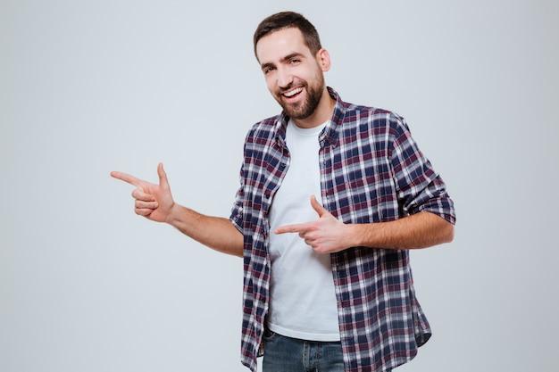 Glücklicher bärtiger mann im hemd, das weg zeigt