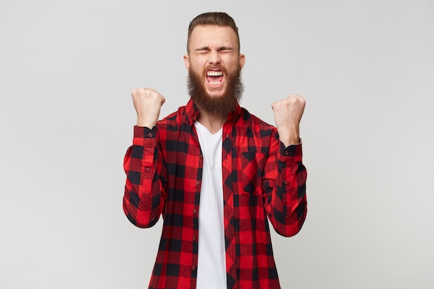 Glücklicher bärtiger mann im karierten hemd ballt die fäuste wie sieger mit geschlossenen augen vor vergnügen, schreit über seinen sieg feiert seinen sieg, isoliert über weißem hintergrund