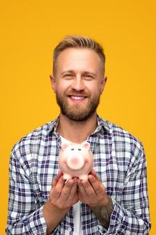 Glücklicher bärtiger mann im karierten hemd, der sparschwein mit geld zeigt und für kamera lächelt