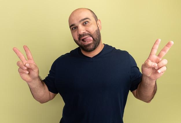 Glücklicher bärtiger mann im lächelnden schwarzen t-shirt, das zunge herausragt, die v-zeichen zeigt, das über grüner wand steht