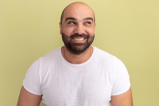 Glücklicher bärtiger mann im weißen t-shirt, das mit lächeln auf gesicht steht, das über grüner wand steht