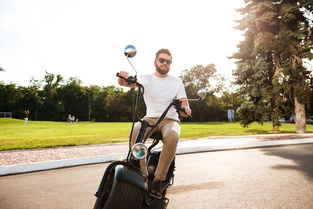 Glücklicher bärtiger mann in der sonnenbrille reitet auf modernem motorrad im freien und schaut weg