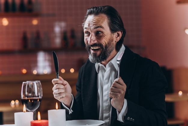 Glücklicher bärtiger mann in einer klage, die an einem tisch in einem restaurant mit einem messer und einer gabel in seinen händen sitzt