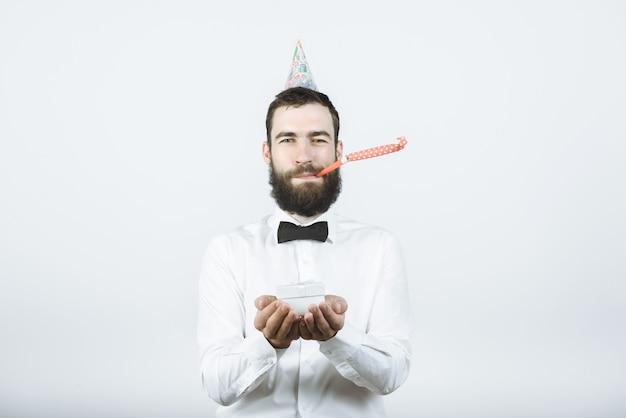 Glücklicher bärtiger mann in party- oder geburtstagskappen bläst ein horn und hält ein geschenk in seinen händen