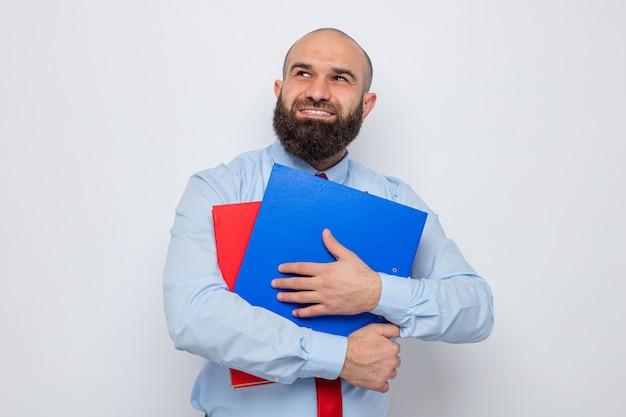 Glücklicher bärtiger mann in roter krawatte und blauem hemd, der büroordner hält und mit einem lächeln im gesicht träumt
