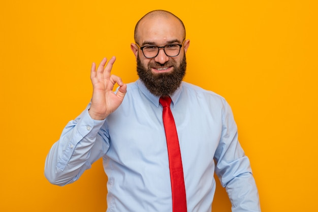 Glücklicher bärtiger mann in roter krawatte und blauem hemd mit brille, der mit einem lächeln schaut und ein ok zeichen zeigt