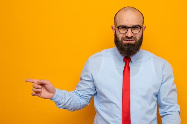 Glücklicher bärtiger mann in roter krawatte und hemd mit brille und blick auf die kamera, die mit dem zeigefinger auf die seite zeigt und selbstbewusst auf orangefarbenem hintergrund steht