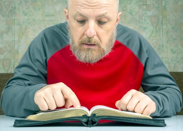 Glücklicher bärtiger mann studiert die bibel. religion und christentum.