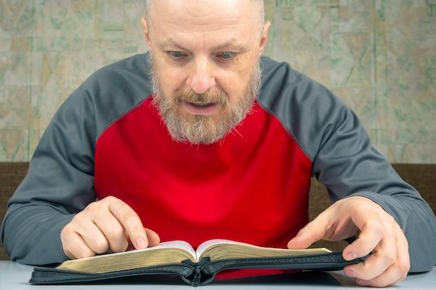 Glücklicher bärtiger mann studiert die bibel. religion und christentum