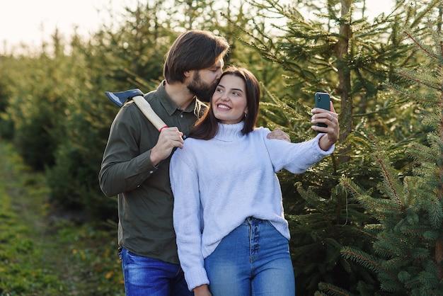 Glücklicher bärtiger mann und seine hübsche freundin machen selfie-foto auf weihnachtsbaumplantage