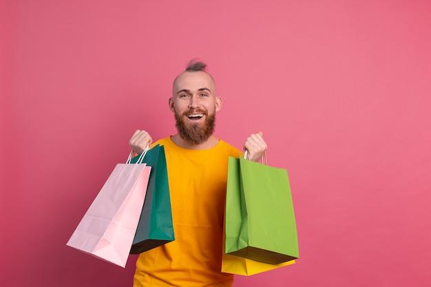 Glücklicher bärtiger positiver mann lässiger blick mit buntem einkaufstaschenstudio rosa hintergrund