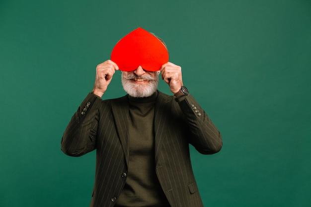 Glücklicher bärtiger und reifer mann des schnurrbartes im khakifarbenen anzug schließt augen rotes herzgruß valentine isolierte grünen hintergrund.