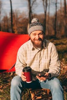 Glücklicher bärtiger wanderer mit smartphone und tasse im wald