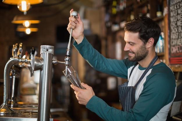 Glücklicher barkeeper, der bier vom zapfhahn gießt