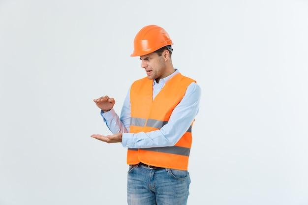 Glücklicher bartingenieur, der hand auf der seite hält und etwas erklärt, kerl mit caro-shirt und jeans mit gelber weste und orangefarbenem helm, isoliert auf weißem hintergrund.