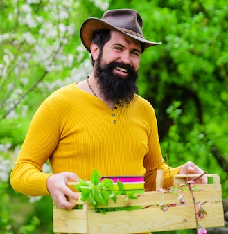 Glücklicher bauer im frühlingsgarten. bärtiger mann mit kiste. öko-bauernhof. gärtner arbeiten.