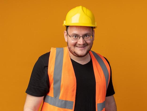 Glücklicher baumeister in bauweste und schutzhelm mit blick auf die kamera, die fröhlich über orange steht