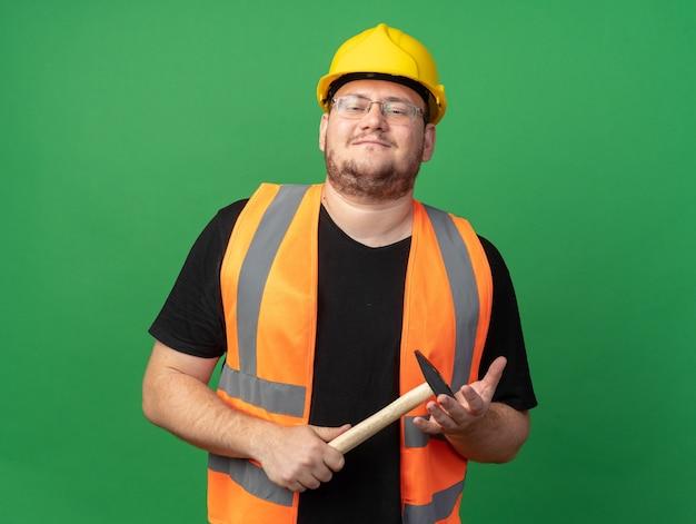 Glücklicher baumeister in bauweste und schutzhelm mit hammer, der die kamera ansieht und selbstbewusst auf grünem hintergrund steht