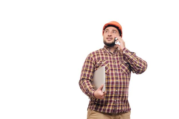 Glücklicher baumeisterarbeiter in der schutzkonstruktion orange helm, der einen laptop hält und am telefon spricht, lokalisiert auf weißem hintergrund. kopieren sie platz für text. zeit zu arbeiten.